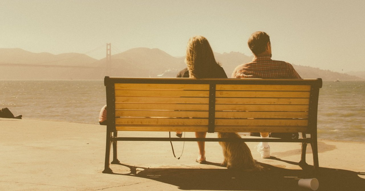Couple sitting on bench on cloudy day