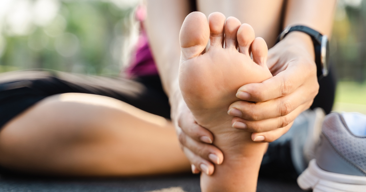 Athletic woman rubbing the bottom of her foot