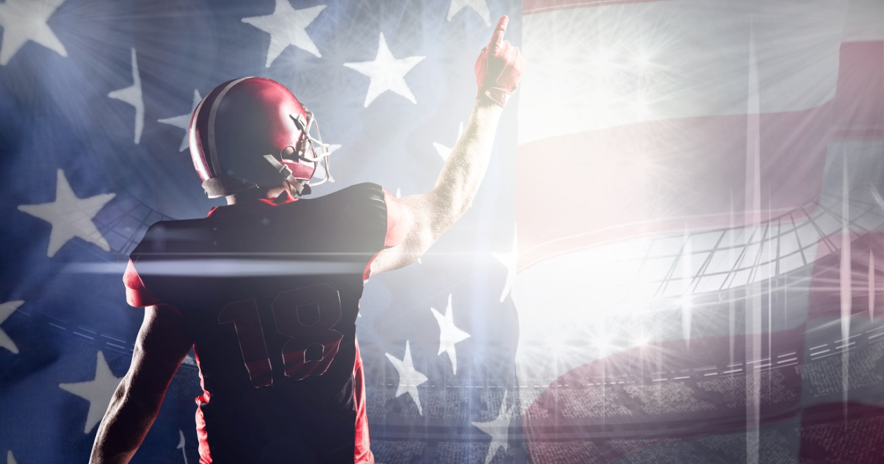 Football player with his finger to the sky and American flag in the background